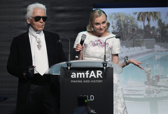 Karl Lagerfeld and Diane Kruger auction off items for the amfAR Cinema Against AIDS benefit during the 65th Cannes film festival in Cap d'Antibes, southern France, on Thursday. The gala raised a record-breaking $11 million for AIDS research, organizers said Friday. (Associated Press)
