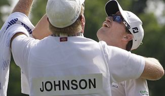 Zach Johnson, right, celebrates with caddie Damon Green after winning the PGA Colonial golf tournament on Sunday, May 27, 2012, in Fort Worth, Texas. (AP Photo/LM Otero)