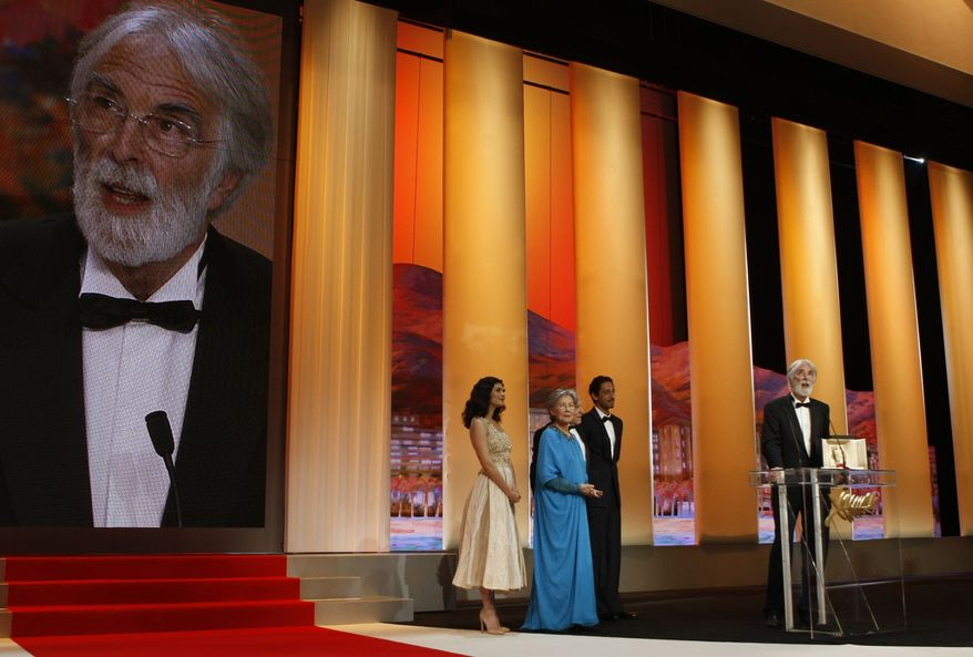 """Film director Michael Haneke (right) receives the first-place Palme d'Or for """"Amour"""" at the 65th Cannes Film Festival in Cannes, France, on Sunday, May 27, 2012. Also onstage are (from left) actresses Audrey Tautou and Emmanuelle Riva and actors Jean-Louis Trintingant (partially seen) and Adrien Brody. (AP Photo/Lionel Cironneau)"""