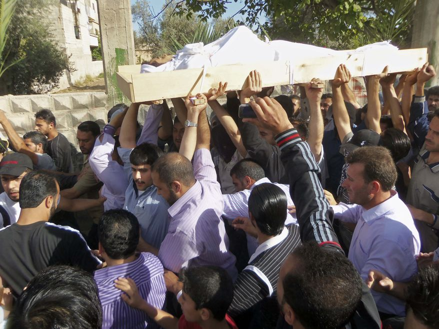 Mourners chant slogans against the Syrian regime as they carry the body of soldier Khaled Shurbajy, who was shot by Syrian security forces in Dir el Zour last week after disobeying orders to fire on anti-Assad protesters, during his funeral procession in the Kfar Suseh area of Damascus, Syria, on Saturday, May 26, 2012. (AP Photo)