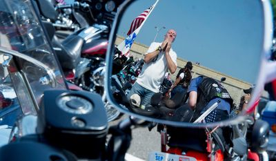 John Ashton of Stawell, Victoria, Australia is seen reflected in the mirror of a motorcycle as he puts sunscreen on his face while waiting to ride in the 25th Rolling Thunder event. Ashton was visiting a friend who lives in New York, and the two of them came down to ride. (Barbara L. Salisbury/The Washington Times)