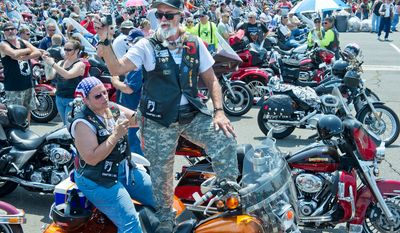 While his wife Jaye holds a hand out to steady him, Harry Williams of Fayetteville, N.C. stands up on the back of his motorcycle to get a picture of all of the bikers in the Pentagon parking lot who are waiting to start the annual Rolling Thunder ride. The bikes leave the Pentagon and travel into town, ending up at the Vietnam Wall. (Barbara L. Salisbury/The Washington Times)
