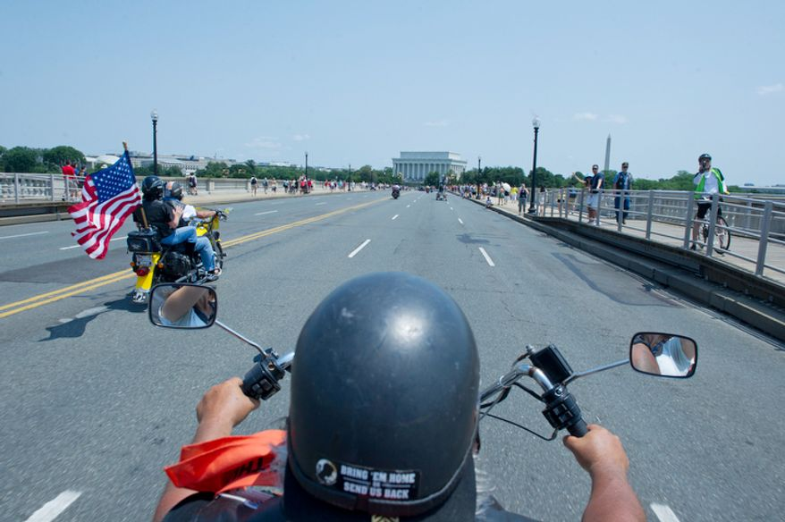 Mike Evangelho, of Brick, N.J. makes his way across the Memorial Bridge during the annual Rolling Thunder event. This is the fifth year he has ridden. Although he was unable to serve in the military because of poor eyesight, he lost many friends and family members in combat and says he comes down to support the soldiers. (Barbara L. Salisbury/The Washington Times)