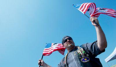 Craig Hardy with Rolling Thunder North Carolina Chapter 1 sells 25th anniversary Rolling Thunder flags. (Barbara L. Salisbury/The Washington Times)