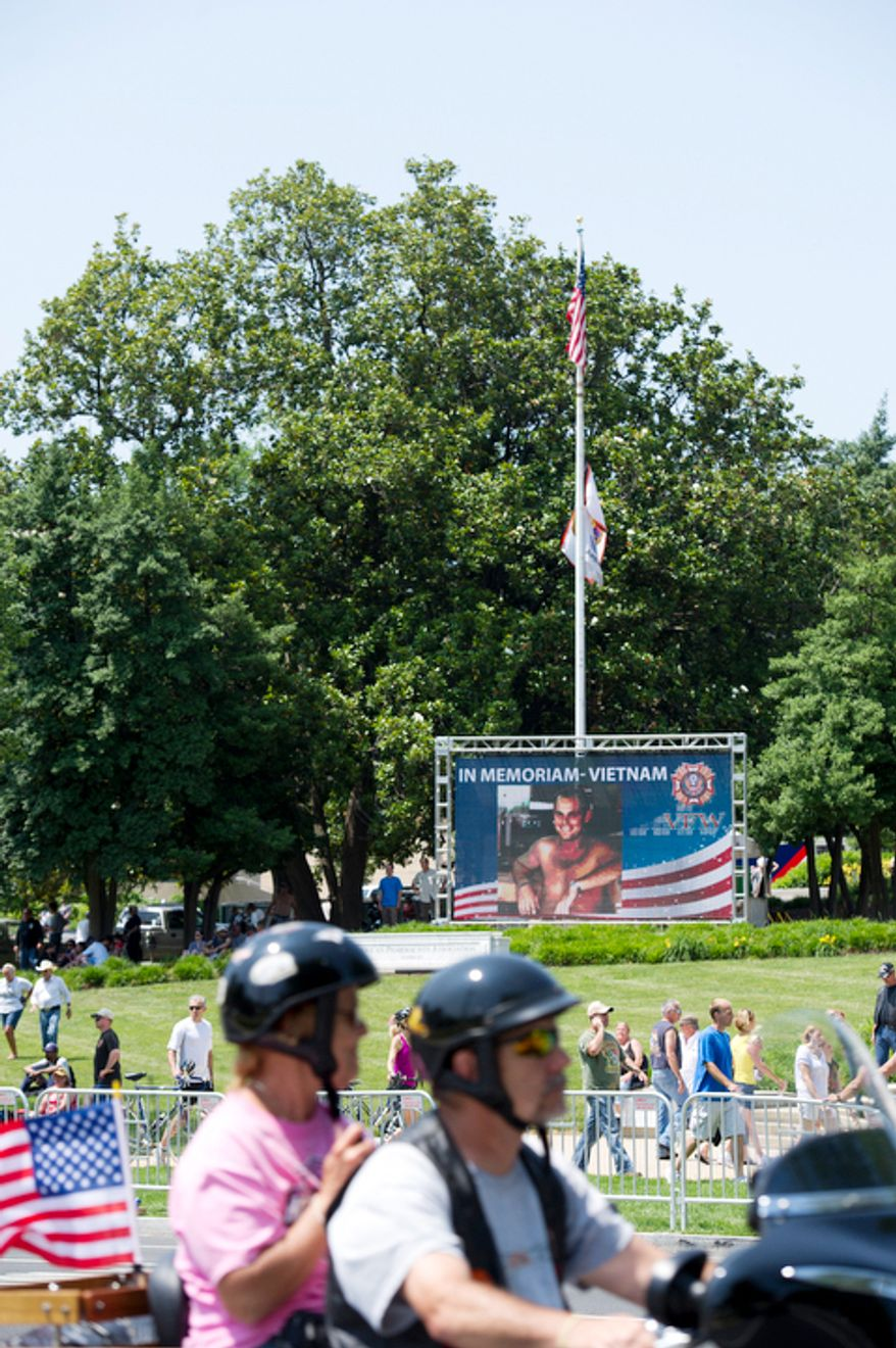 Bikers ride past a memorial screen along Constitution Avenue in Washington, D.C. during the 25th anniversary of Rolling Thunder on Sunday, May 27, 2012.  (Barbara L. Salisbury/The Washington Times)