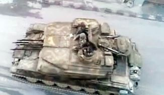 "SHAAM NEWS NETWORK VIA ASSOCIATED PRESS This image made from amateur video, which could not be verified by the AP, purports to show a Syrian tank in Damascus, Syria. A U.N. envoy called Monday on ""every individual with a gun"" in Syria to lay down arms."