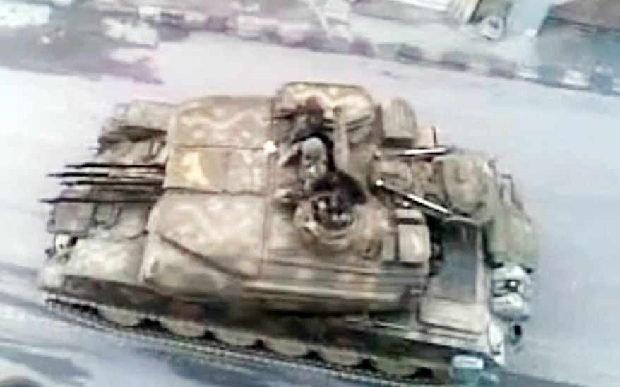 """SHAAM NEWS NETWORK VIA ASSOCIATED PRESS This image made from amateur video, which could not be verified by the AP, purports to show a Syrian tank in Damascus, Syria. A U.N. envoy called Monday on """"every individual with a gun"""" in Syria to lay down arms."""