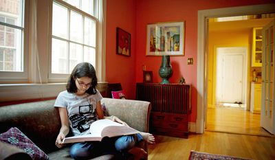 """Tuli Bennett-Bose, 12, reads from the dictionary as she waits for her father to join her to practice her spelling at their D.C. home. """"I learn by a mix of everything: visually, hearing it, saying it and feeling it,"""" says the seventh-grader at Oyster-Adams Bilingual School, who is fluent in four languages. (Rod Lamkey Jr./The Washington Times)"""