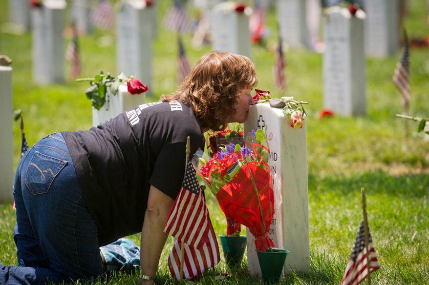 Karen Clarkson, of Fairbanks, Alaska, kisses the headstone of her son U.S. Army Sergeant Joel Clarkson on Memorial Day at Arlington National Cemetery in Arlington, Va., Monday, May 28, 2012. (Rod Lamkey Jr/The Washington Times)