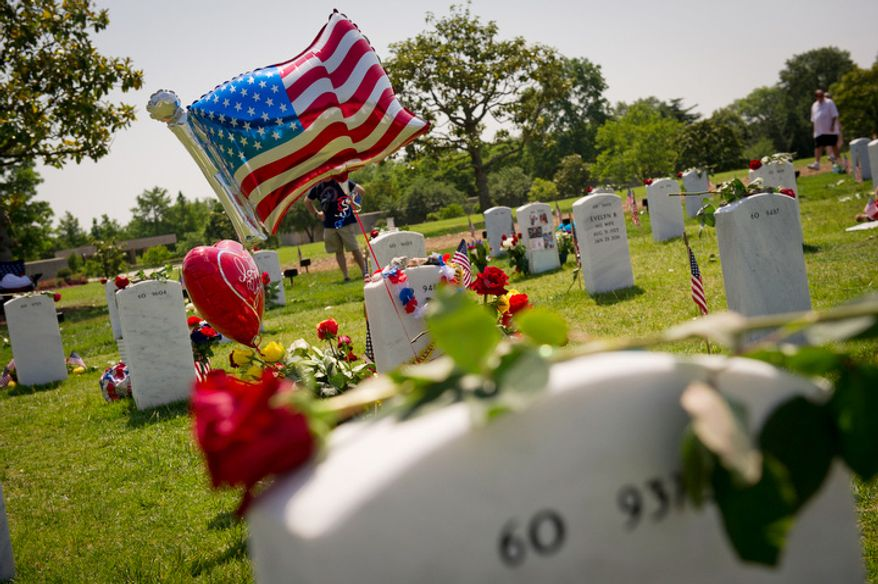 A balloon and flowers decorate a grave site on Memorial Day. (Rod Lamkey Jr/The Washington Times)
