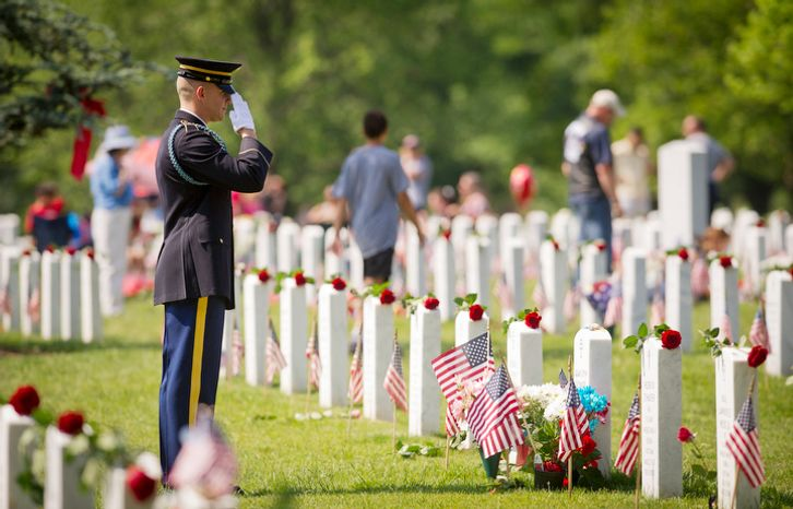 A member of the U.S. Army salutes a grave site on Memorial Day at Arlington National Cemetery. (Rod Lamkey Jr/The Washington Times)