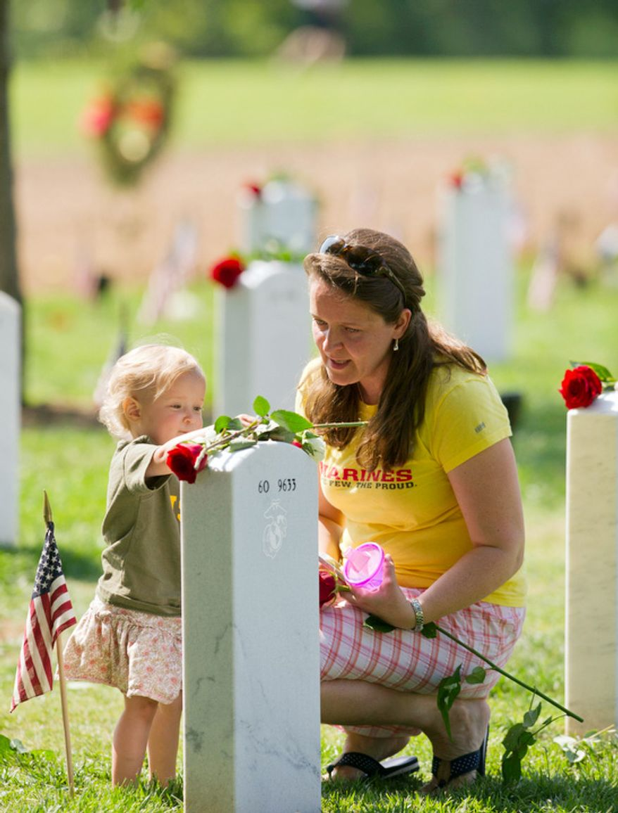 Tracey Crosby, of Potomac Falls, Va., is joined by her 17 month-old daughter Rachel as they visit the grave of her cousin, U.S. Marine  Staff Sergeant Nick Sprovtsoff on Memorial Day at Arlington National Cemetery. Mr. Sprovtsoff  was killed on September 28, 2011 during his fifth tour in Afghanistan. (Rod Lamkey Jr/The Washington Times)