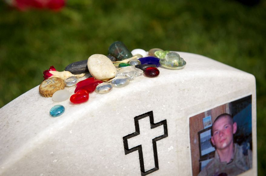 Rocks and colorful glass stones decorate the top of the headstone of U.S. Marine Corps. Lance Corporal Eric William Herzberg. (Rod Lamkey Jr/The Washington Times)