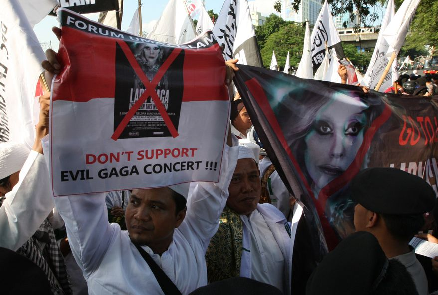 Muslim men hold up banners during a rally against U.S. pop singer Lady Gaga's concert that is scheduled to be held on June 3, outside the U.S. Embassy in Jakarta, Indonesia, Friday, May 25, 2012. Lady Gaga wound up cancelling her sold-out show in Indonesia amid concerns her sexy clothes and dance moves undermine Islamic values and will corrupt the country's youth. (AP Photo/Dita Alangkara)