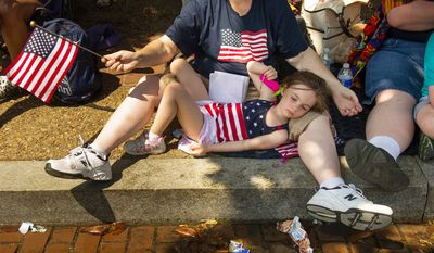 Abby Ridgeway, 6, of Woodbridge, Md., tries to stay cool as she lays in the lap of her mother, Jill, as they watch the Memorial Day Parade. (Andrew Harnik/The Washington Times)