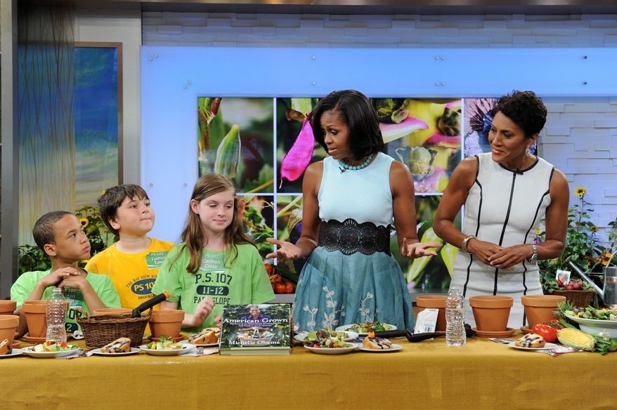 """First lady Michelle Obama talks to children about food during an appearance in May 2012 with host Robin Roberts (right) on """"Good Morning America."""" Mrs. Obama's book, """"American Grown: The Story of the White House Kitchen Garden and Gardens Across America,"""" was being released. (ABC via Associated Press)"""