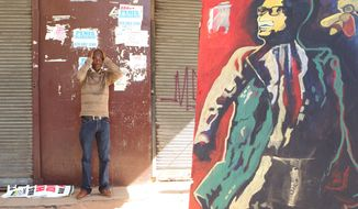 A man stands a next to an attempted copy of the offending art work by an unidentified artist of ruling party African National Congress (ANC) president Jacob Zuma outside the South Gauteng High Court in Johannesburg, South Africa on Thursday May 24, 2012. President Jacob Zuma is asking the High Court to issue an order that display of the now-defaced painting violates his constitutional right to dignity. The gallery and the artist counter that freedom of expression, also protected by the constitution, is at stake. (AP Photo/Themba Hadebe)