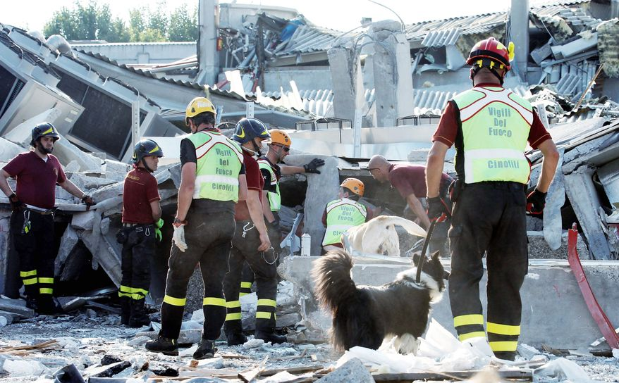 Rescue teams use dogs as they look for three workers reported missing at a factory in Medolla, Italy, after a magnitude 5.8 earthquake struck the same area shaken by a larger tremor nine days earlier. (Associated Press)