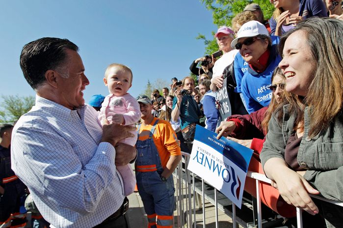 Former Massachusetts Gov. Mitt Romney, the presumptive Republican presidential candidate, holds a baby as he greets supporters after speaking at a campaign event in Craig, Colo., on Tuesday. (Associated Press)