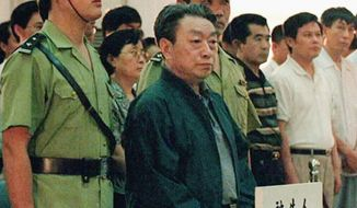Former Beijing Mayor Chen Xitong (center) stands in Municipal Higher Peoples Court in Beijing in July 1998. Chen was deposed as Beijing's Communist Party boss for corruption and is serving a 16-year prison sentence. (AP Photo/Xinhua News Agency)