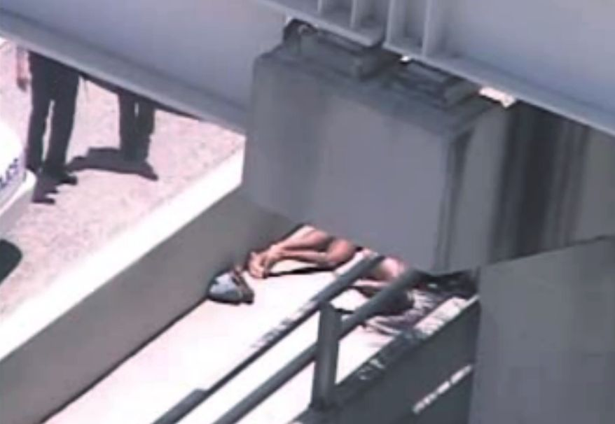 In this image taken from video, Miami police officers (left) stand watch near a naked man (second from right) who was shot dead by a police officer when he refused to stop chewing on the face of another naked man (partially obscured by a railing) on the MacArthur Causeway ramp in Miami on Saturday, May 26, 2012. (AP Photo/Miami Herald)