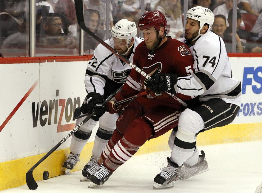 Los Angeles Kings Trevor Lewis (22) and Dwight King (74) pressure Phoenix Coyotes defenseman Derek Morris on the forecheck in the Western Conference final series. (AP Photo/Ross D. Franklin)