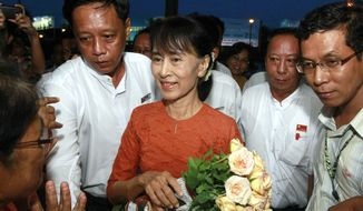 Myanmar opposition leader Aung San Suu Kyi (center) is greeted by a supporter upon her arrival at Yangon International Airport in Yangon, Myanmar, on her way to Bangkok on Tuesday, May 29, 2012. The trip is her first outside Myanmar in 24 years. (AP Photo/Khin Maung Win)