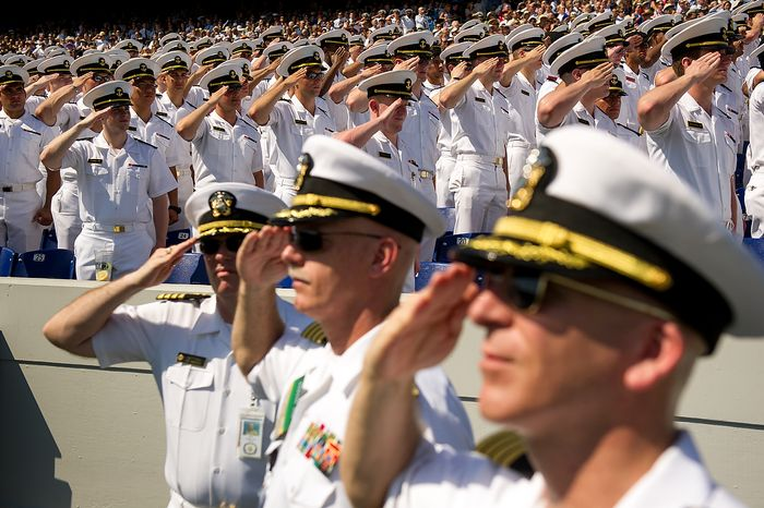 Naval officers salute for the playing of the National Anthem at the graduation ceremony for the U.S. Navy Academy's class of 2012 at the Navy-Marine Corps Stadium, Annapolis, Md., Tuesday, May 29, 2012. (Andrew Harnik/The Washington Times)