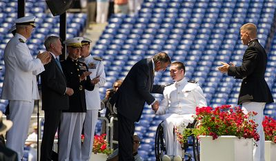 Midshipman Kevin Joseph Hillery, who was paralyzed from the waist down in his junior year by a falling tree, shakes hands with U.S. Secretary of Defense Leon Panetta, third from right, has he takes the stage to receive his diploma during the Graduation ceremony the U.S. Naval Academy's class of 2012 at the Navy-Marine Corps Stadium, Annapolis, Md., Tuesday, May 29, 2012. (Andrew Harnik/The Washington Times)