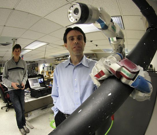 ** FILE ** In this April 18, 2012, photo, Carnegie Mellon University professor Howie Choset, right, stands beside a robot as staff researcher Florinan Enner uses a controller to demonstrate how it climbs up a tubular armature at their lab on campus in Pittsburgh. Scientists and doctors are using the creeping metallic tools to perform surgery on hearts, prostate cancer and other diseased organs. (AP Photo/Keith Srakocic)