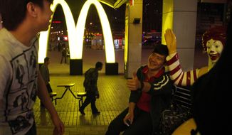 ** FILE ** Youths hang out near a McDonald's restaurant at a train station in Shenyang in northern China's Liaoning province. (Associated Press)