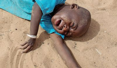 Wanting food, of which there is none, 2-year-old Aliou Seyni Diallo collapses in tears in the Senegal village of Goudoude Diobe.