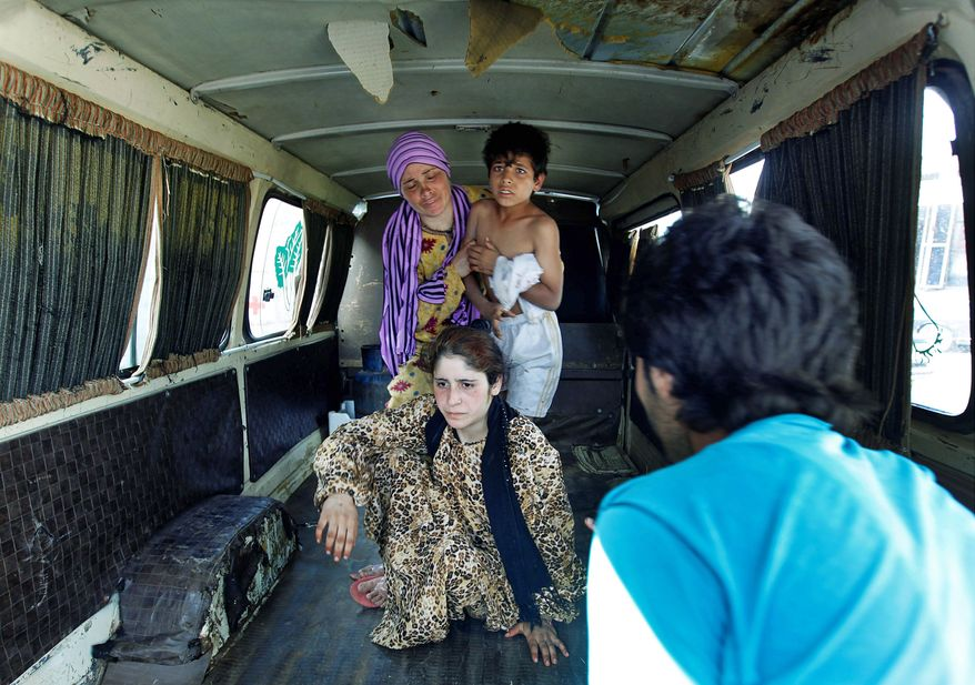 A Lebanese man (right) helps a Syrian family on Wednesday after they were shot by a Syrian border guard when they were crossing a river from Syria into Lebanon at the northern Lebanese-Syrian border town of Wadi Khaled in Akkar. (Associated Press)