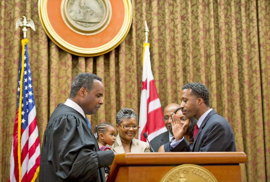 Judge Erik P. Christian of the D.C. Superior Court swears in Mr. McDuffie on Wednesday at the John A. Wilson Building. With him on the dais were his wife, daughter and parents. (Barbara L. Salisbury/The Washington Times)