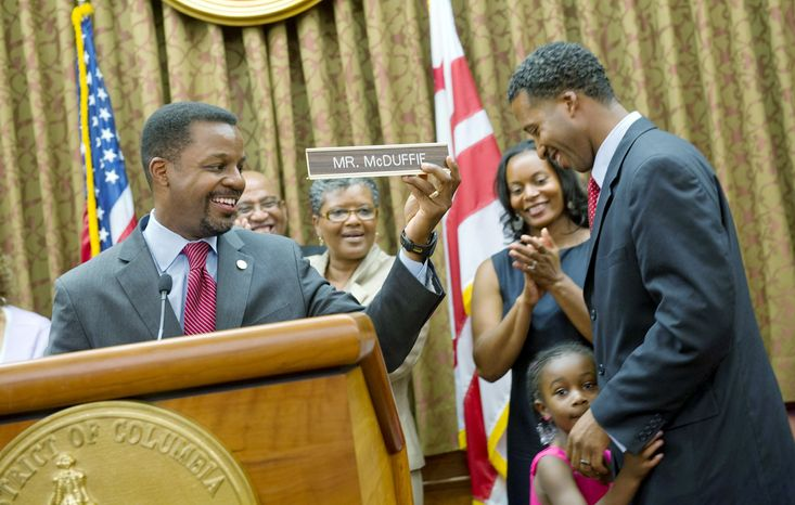 """D.C. Council Chairman Kwame R. Brown holds up the new """"Mr. McDuffie"""" nameplate for Kenyan McDuffie, the newest member of the D.C. Council who was sworn in Wednesday. With Mr. McDuffie are his wife, Princess, and daughter Jozi. """"I know where we are today, but I also know how far we have to go,"""" the new Ward 5 member said upon taking over for his convicted predecessor Harry Thomas Jr. (Barbara L. Salisbury/The Washington Times)"""