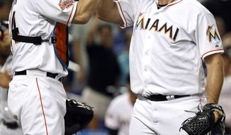 Miami Marlins relief pitcher Heath Bell celebrates with catcher John Buck after the Marlins defeated the Washington Nationals 3-1 on Tuesday, May 29, 2012, in Miami. (AP Photo/Lynne Sladky)