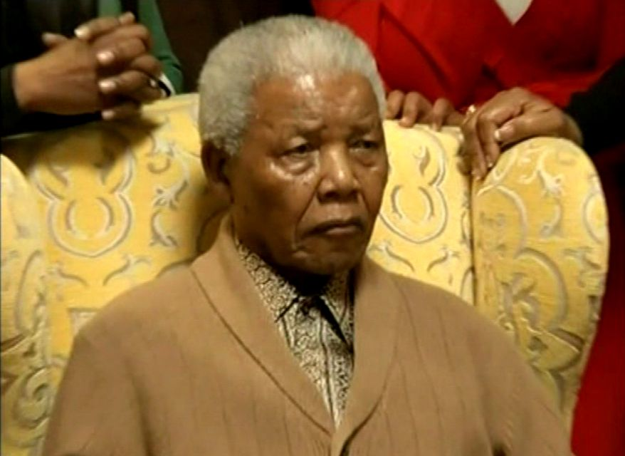 Former South African president Nelson Mandela receives a torch May 30, 2012, to celebrate the African National Congress' centenary in his home village of Qunu in rural eastern South Africa. (Associated Press/SABC via AP video)
