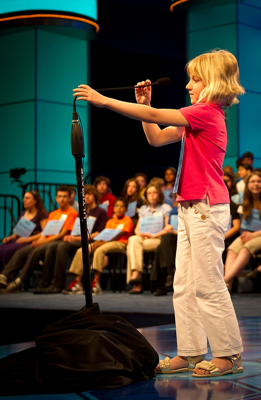 Six year-old Lori Anne C. Madison of Woodbridge, Va., works on adjusting the height of the tall microphone during round two of the 2012 Scripps National Spelling Bee at the Gaylord National Resort and Convention Center in National Harbor, Md., Wednesday, May 30, 2012. This year, 278 spellers from around the United States and all walks of life will compete for the title of 2012 Scripps National Spelling Bee champion. Lori Anne spelled her word, dirigible, correctly. (Rod Lamkey Jr/The Washington Times)