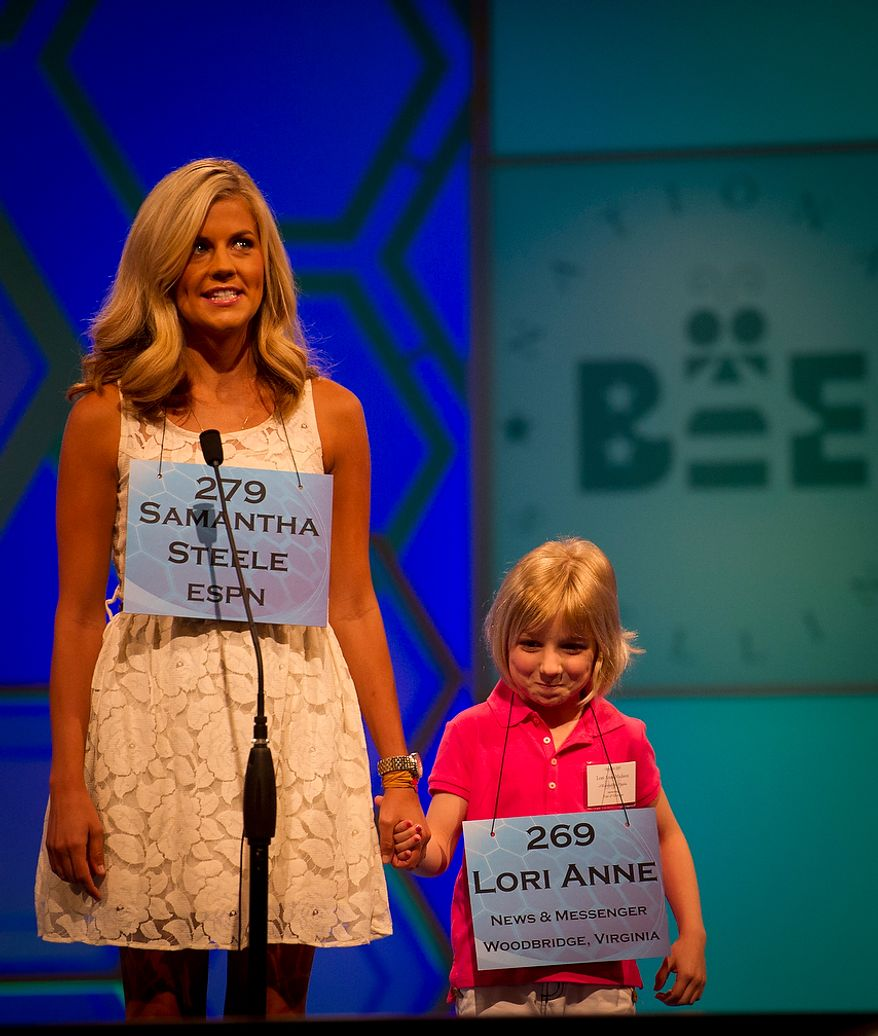 Six year-old Lori Anne C. Madison of Woodbridge, Va., is joined on stage as ESPN's Samantha Steele appears as a guest speller during the preliminary rounds of the 2012 Scripps National Spelling Bee at the Gaylord National Resort and Convention Center in National Harbor, Md., Wednesday, May 30, 2012. This year, 278 spellers from around the United States and all walks of life will compete for the title of 2012 Scripps National Spelling Bee champion. (Rod Lamkey Jr/The Washington Times)