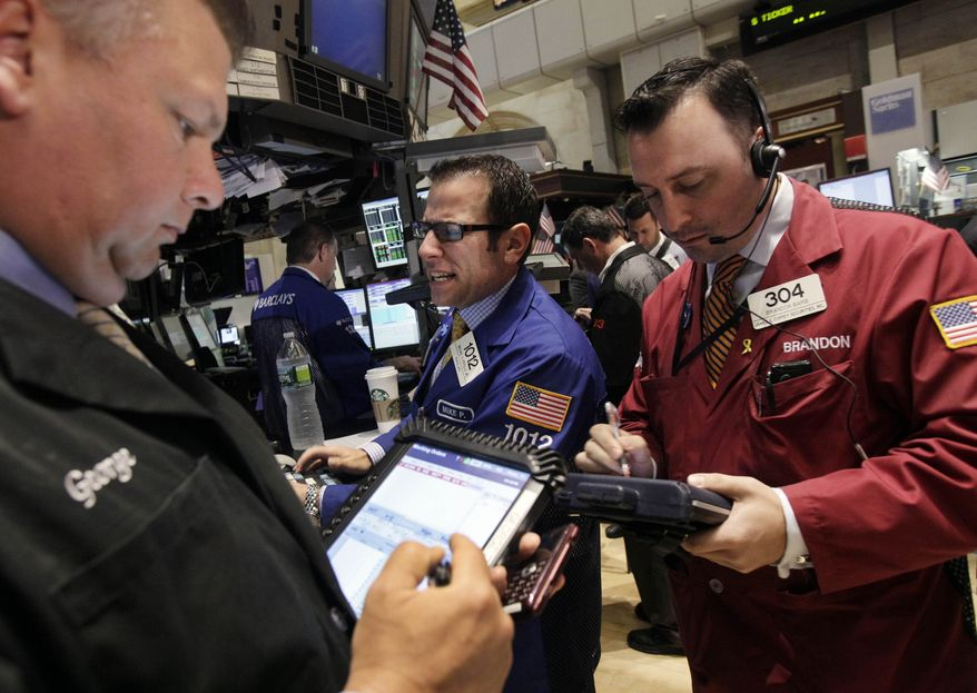 Specialist Michael Pistillo (center) works May 30, 2012, at his post on the floor of the New York Stock Exchange. (Associated Press)