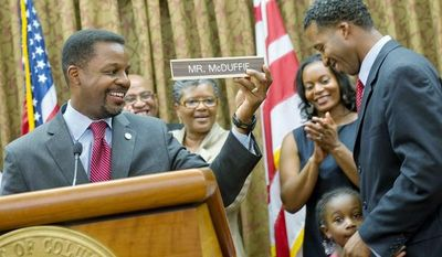 "D.C. Council Chairman Kwame R. Brown holds up the new ""Mr. McDuffie"" nameplate for Kenyan McDuffie, the newest member of the D.C. Council who was sworn in Wednesday. With Mr. McDuffie are his wife, Princess, and daughter Jozi. ""I know where we are today, but I also know how far we have to go,"" the new Ward 5 member said upon taking over for his convicted predecessor Harry Thomas Jr. (Barbara L. Salisbury/The Washington Times)"