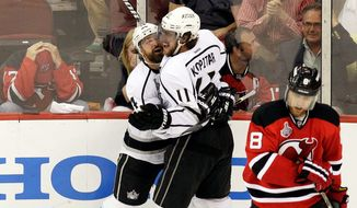 associated press Los Angeles' Anze Kopitar (11) celebrates with Justin Williams after scoring in overtime to beat New Jersey 2-1 on Wednesday, the Kings' ninth straight road win. The Kings' shutdown style also has worked in Vancouver, St. Louis and Phoenix.