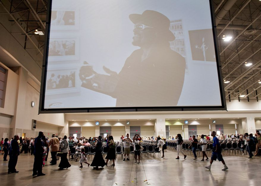 The image of musician Chuck Brown looms over relatives, friends and fans Thursday as they leave the Washington Convention Center after a memorial service. A crowd of more than 9,000 attended the nearly four-hour-long event honoring Brown. (Barbara L. Salisbury/The Washington Times)