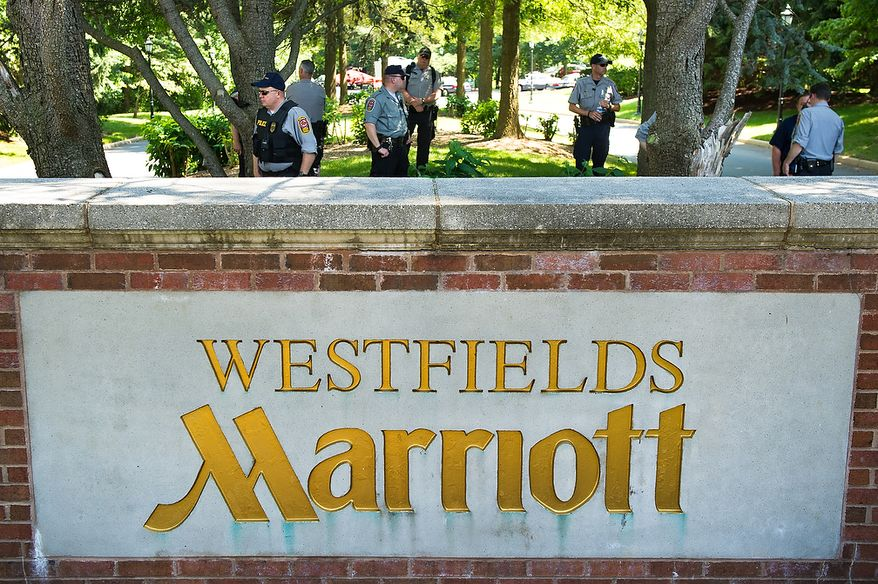 Police officers stand guard at the entrance to the Marriott Westfields where the annual Bilderberg Conference is being held, Chantilly, Va., Thursday, May 31, 2012. The Bilderberg Conference is an annual meeting of highly influential people in private industry and public office from North America and Western Europe. (Andrew Harnik/The Washington Times)