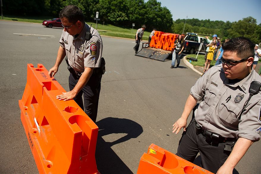 Police officers set up orange barriers as protesters gather at the entrance to the Marriott Westfields where the annual Bilderberg Conference is being held, Chantilly, Va., Thursday, May 31, 2012. The Bilderberg Conference is an annual meeting of highly influential people in private industry and public office from North America and Western Europe. (Andrew Harnik/The Washington Times)