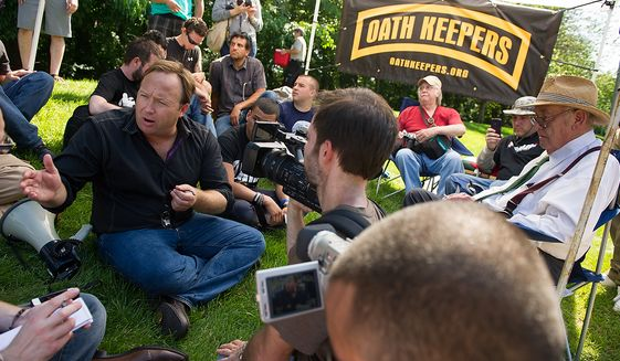 Alex Jones, a radio personality and conspiracy theorist, left, and Jim Tucker, an auther and journalist who has been writing about the Bilderberg Conference since 1975, right, speaks with protesters and members of the media during a demonstration at the entrance to the Marriott Westfields where the annual Bilderberg Conference is being held, Chantilly, Va., Thursday, May 31, 2012. (Andrew Harnik/The Washington Times)