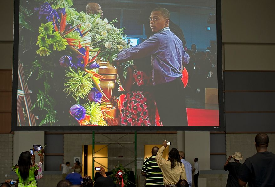 People take pictures with cell phones as Chuck Brown's grandson is seen on the large screen approaching the casket during the memorial service for D.C. Go Go icon Chuck Brown Thursday, May 31, 2012 at the Washington Convention Center in Washington, D.C. Thousands of people came out to say goodbye to the D.C. legend. (Barbara L. Salisbury/The Washington Times)