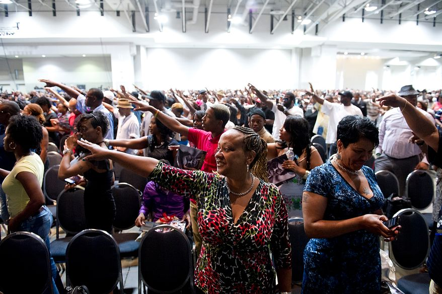 People at the memorial service for D.C. Go-Go icon Chuck Brown raise their hands towards his family to bring blessings upon them. The service was held Thursday, May 31, 2012 at the Washington Convention Center in Washington, D.C. Thousands of people came out to say goodbye to the D.C. legend. (Barbara L. Salisbury/The Washington Times)