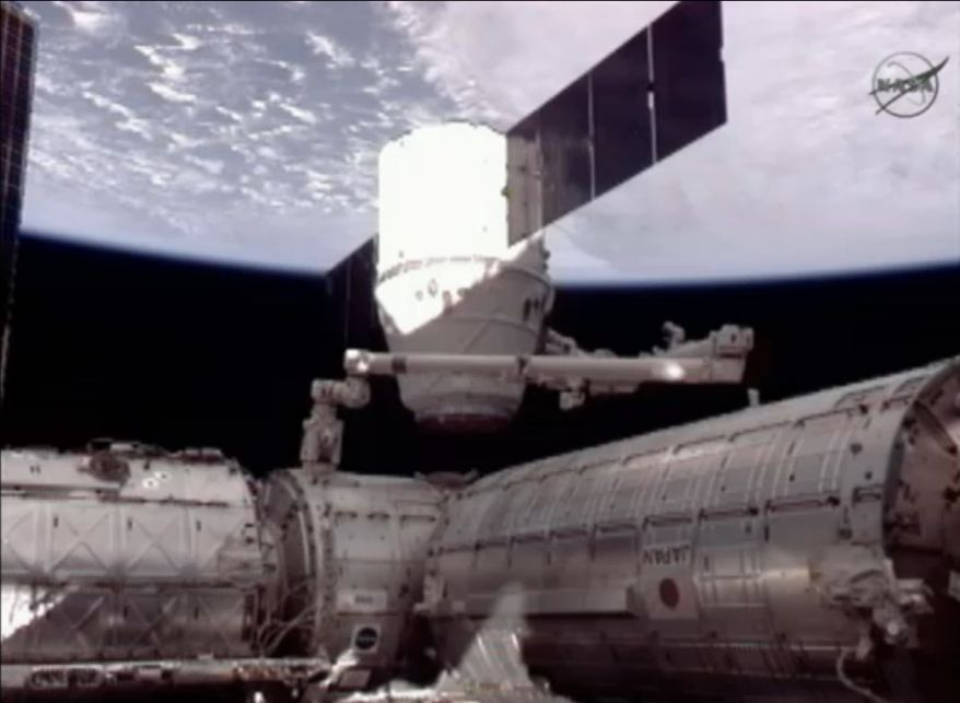 This frame grab image from NASA-TV shows the SpaceX Dragon capsule, center, the U.S. Destiny lab, left and the Japanese Kibo module, right just after the Dragon capsule was dematted from the International Space Station Thursday, May 31, 2012. (AP Photo/NASA)