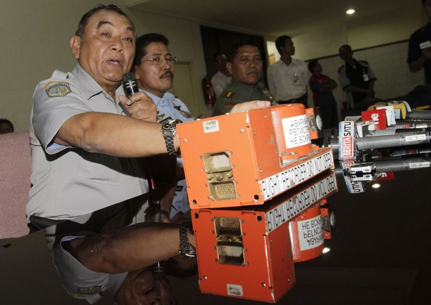 Indonesian National Transportation Safety Board chief Tatang Kurniadi (left), with the flight data recorder of the crashed Sukhoi Superjet 100, speaks May 31, 2012, during a press conference in Jakarta, Indonesia. Authorities found the flight data recorder of the Russian plane that slammed into a jungle-clad cliff atop an Indonesian volcano during a May 9 demonstration flight for potential buyers. (Associated Press)